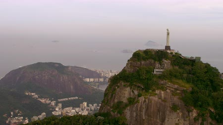 initial : Aerial side view of Christ the Redeemer - Rio de Janeiro, Brazil. The landscape in the foreground of the shot is finely tuned, sharp, and colorful. A bird passes through the initial portion of the shot. Stock Footage