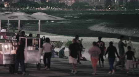 Рио : Close up static shot of street vendors and pedestrians on copacobana beach. Filmed at night. Food vendors are pushing carts on sidewalk. City is illuminated in background. waves are white and crashing into the shore. Umbrellas are visible near food vendor