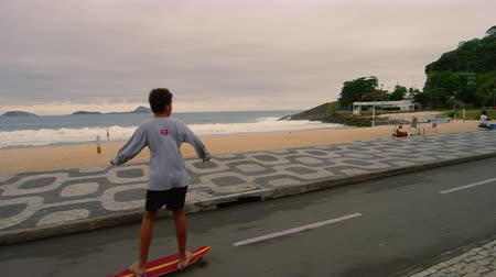 Рио : Slow motion dolly shot of boy skateboarding on Avenida Vieira Souto near Ipanema Beach in Rio de Janeiro, Brazil