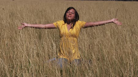 pozisyon : Woman with out stretched arms and eyes closed sits in a relaxing position in a wheat field Stok Video