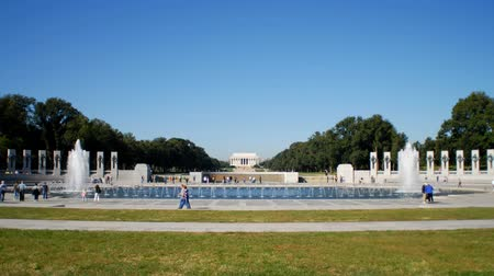 druhé světové války : People surround the historic National World War II Memorial with fountain and stone structures commemmorating soldiers and War heroes in Washington DC with green trees and Lincoln Memorial in background, with blue sky above. Dostupné videozáznamy