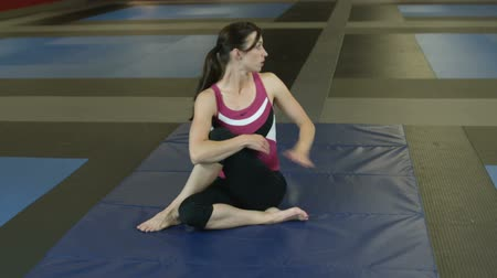 esneme : Girl in a gym sitting on the floor and stretching