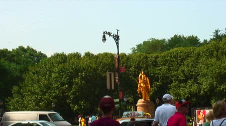 дорожный знак : Zoom out shot from birds perched on a lamppost to showing a golden statue and people near Central Park, New York City.