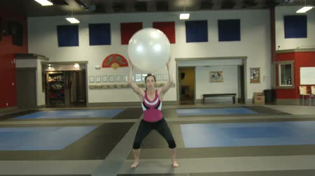 aerobik : Full body shot of a girl in a gym working out doing squats holding a fitness ball above her head Stok Video