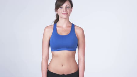 skóra : Front view panning shot down of a smiling white female against a white background wearing gym clothes