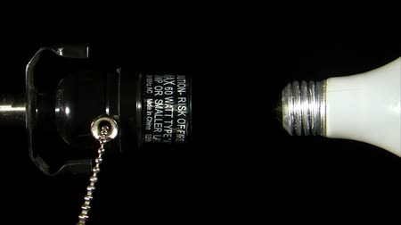 izzók : A static shot of a lamp socket and a detached light bulb. The pull string is swinging and there is a black background. Stock mozgókép