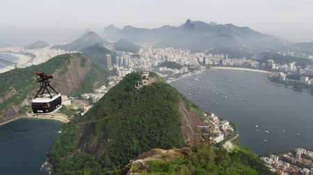 Рио : Gondola going up the side of Sugarloaf Mountain in Rio de Janeiro, Brazil. Lagoa Rodrigo de Freitas is seen in the background.