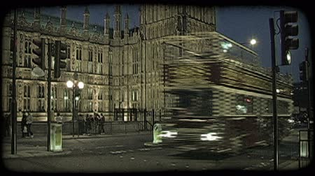 dvojitý : English double decker buses, cars, and people crossing the lit street adjoining the English Parliament in London, England at dusk. Vintage stylized video clip.