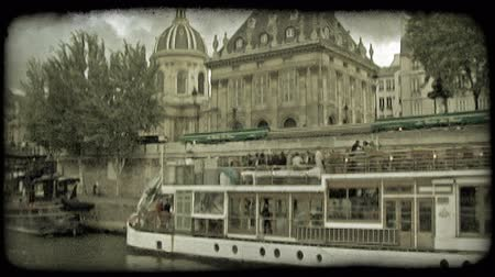 paříž : Panoramic view of Paris, France historic building from boat with other long boat in foreground, and dramatic cloud background from river. Vintage stylized video clip.