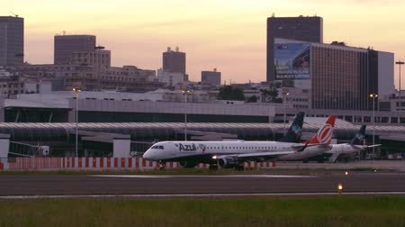 azul : Static shot as a plane can be seen from a distance taxiing down the tarmac. Another plane is backing out of its terminal behind it. Stock Footage