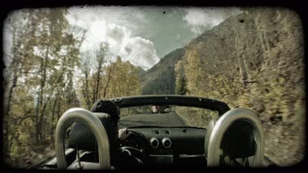 múlt : Man, dressed in black, drives sleek convertible along narrow, bending canyon road past autumn leaves and trees with mountains in backgroung along the Sundance loop in Provo Canyon in Utah. Vintage stylized video clip.