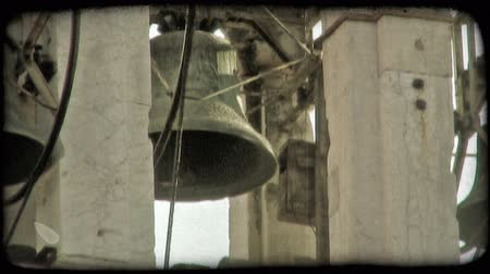 dolgok : Close-up shot of the bells inside of a bell tower in Italy. Vintage stylized video clip.