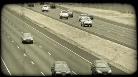 opposite : Cars rush along a three-lane highway or freeway in Salt Lake City, with adjacent freeways each moving in opposite directions in semi-busy traffic on an overcast day. Vintage stylized video clip. Stock Footage