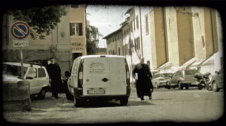 padre : Three religious priests walk through a city street as a car and religious woman pass by. Vintage stylized video clip.