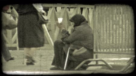 pažba : A begger woman begs as people walk by. Vintage stylized video clip.