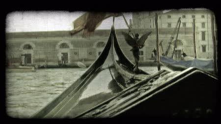 A shot from within a gondola as it cruises down a Venice canal. Vintage stylized video clip.
