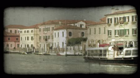 A shot of a large ferry cruising down a Venice canal. Vintage stylized video clip.