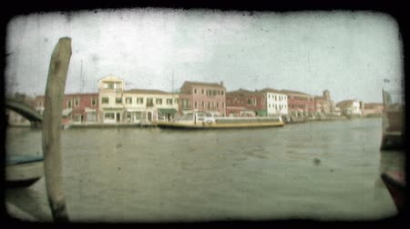 A pan left as a large white and yellow ferry cruising down a Venice canal. Vintage stylized video clip.