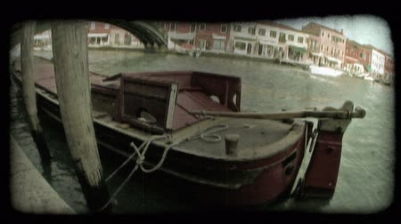 A shot of a unique boat tied to the docks in a Venice canal. Vintage stylized video clip.