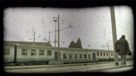 A shot through the window from the inside of an Italian train as people walk by. Vintage stylized video clip.