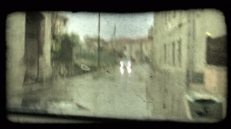 A shot from within a car as it drives down the street and passes other cars on a rainy day in Italy. Vintage stylized video clip.