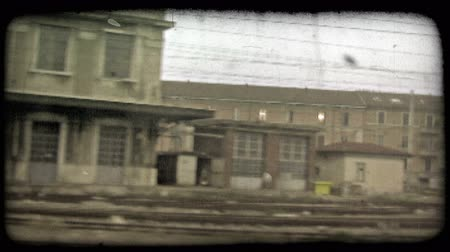 A shot through the window from the inside of an Italian train as it cruises down the track and passes other trains. Vintage stylized video clip.