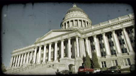 Wide-angle shot of Utah Capitol building from the front left with pillars and staircase leading to its large front doors, as person walks below near parked cars in small parking lot on a sunny day in Salt Lake City, Utah. Vintage stylized video clip. Стоковые видеозаписи