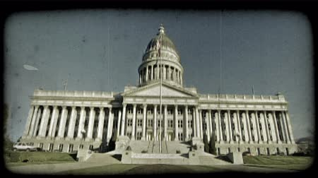 Wide shot of Utah Capitol building from the front with pillars and staircase leading to its large front doors, flag pole in foreground with flag flapping in the wind, and long plot of grass leading to the Capitol steps. Vintage stylized video clip.