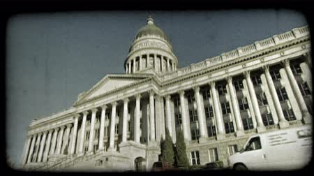 Wide-angle shot of Utah Capitol building from the front left with pillars and staircase leading to its large front doors, as van drives by below, near parked cars in small parking lot on a sunny day in Salt Lake City, Utah. Vintage stylized video clip.