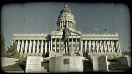 Wide shot of Utah Capitol building from the front with pillars and staircase leading to its large front doors, flag pole with flag flapping in the wind, and bronze dedicatory statue of Ute Native American warrior monument in foreground. Vintage stylized v