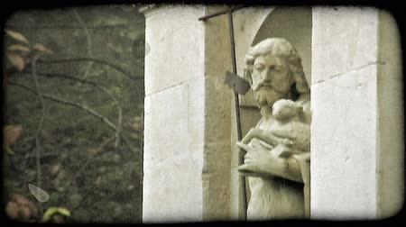 Statue of Christ holding a lamb. Vintage stylized video clip.