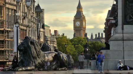 visitantes : Time-lapse shot at Trafalgar Square with people all around. There is a statue of a lion and Big Ben off in the distance in London, England. Filmed in October 2011. Panning shot. Stock Footage