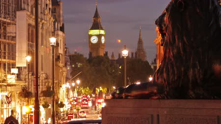 visitantes : Time-lapse shot in the evening at Trafalgar Square. People are walking by and cars are driving by the big lion statue and Big Ben in the distance in London, England. Filmed in October 2011. Panning shot.
