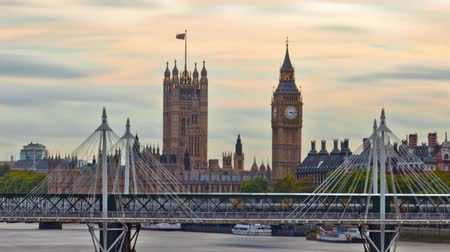 jubileu : Time-lapse shot of Big Ben with the Hungerford Bridge and Golden Jubilee bridges in the foreground. There are boats on the River Thames. Filmed in London in October 2011. Panning shot. Stock Footage