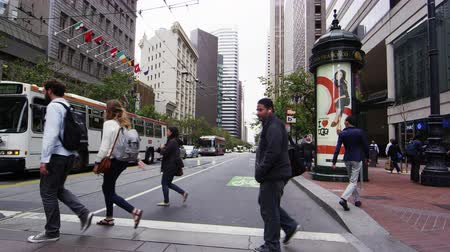 People crossing the street on foot or bike at an intersection in San Francisco Stock Footage