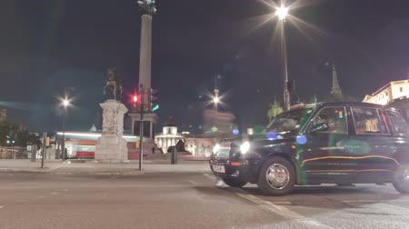 Tracking time-lapse of Nelsons Column filmed from the street at Charing Cross, London. Traffic is passing by around the roundabout. Filmed at night in October 2011. Panning shot. Stok Video