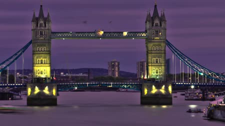 Лондон : A stationary time-lapse of Tower Bridge in London. Buildings and cityscape in the background, traffic on the bridge and boats on the river. The shot starts at sunset with pinkish colors and then it gets darker gradually and the bridge and boats light up.  Стоковые видеозаписи