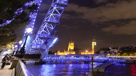 Лондон : Wide angle time-lapse at night of the London Eye Ferris Wheel with Big Ben and the Houses of Parliament in the distant background. The purplish light from the London Eye is reflected in the River Thames. Filmed in October 2011. Cropped.
