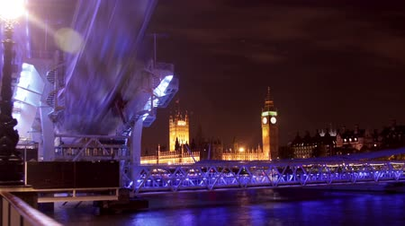 парламент : Motion blurred time-lapse of the London Eye with Big Ben and the Houses of Parliament in the background. Filmed at night when the Ferris wheel is lit in purple and blue light. Filmed in October 2011. Panning shot.