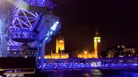 bretanha : Time-lapse of the London Eye with Big Ben and the Houses of Parliament in the background. Filmed at night when the Ferris wheel is lit in purple and blue light. Filmed in October 2011. Cropped.