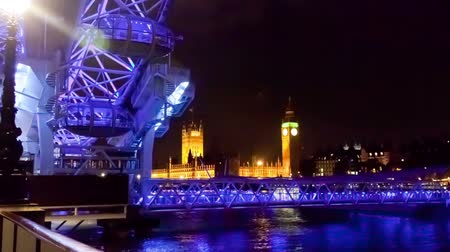 парламент : Time-lapse of the London Eye with Big Ben and the Houses of Parliament in the background. Filmed at night when the Ferris wheel is lit in purple and blue light. Filmed in October 2011. Panning shot. Стоковые видеозаписи