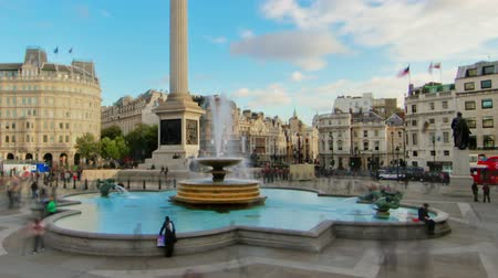 talapzat : Time-lapse of Trafalgar Square in London. People walk around the fountains and Nelsons Column. There is a cloudy yet blue sky overhead. Filmed in October 2011. Cropped. Stock mozgókép