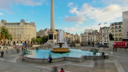 talapzat : Time-lapse of Trafalgar Square in London. People walk around the fountains and Nelsons Column. There is a cloudy yet blue sky overhead. Filmed in October 2011. Panning shot.