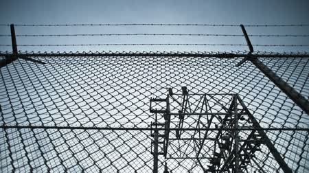 chains : This is a moving timelapse shot of a chain link fence. The camera is tilted upwards showing clouds passing overhead. Stock Footage