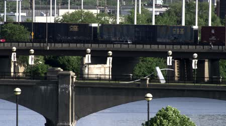 kerék : An old train rattles down the tracks and over the bridge along with cars passing over the river. Stock mozgókép