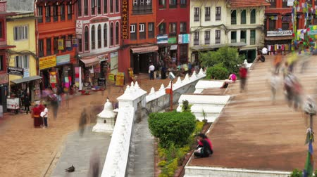 boudha : Time-lapse of people walking around the streets at Boudhanath Stupa in Kathmandu, Nepal. Storefronts can be seen as well as people circling the stupa. Cropped.