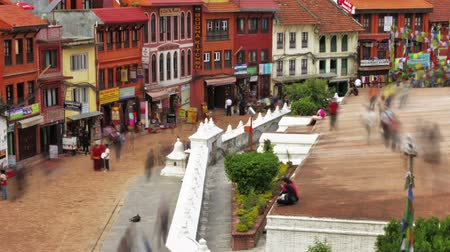 boudha : Time-lapse of people walking around the streets at Boudhanath Stupa in Kathmandu, Nepal. Storefronts can be seen as well as people circling the stupa. Panning shot. Stock Footage