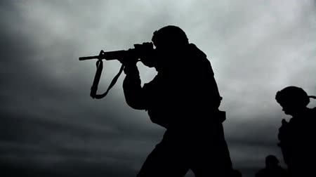 стрельба : Silhouette of soldier, contrasting sky, shooting M4 rifle at shooting range. Green Beret United States Army Special Forces.