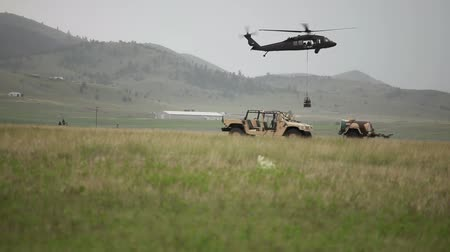pilóta : Black Hawk helicopter dropping cargo in field with Humvee in foreground. Green Beret United States Army Special Forces. Stock mozgókép