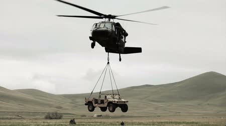 sas : Shot from ground of Black Hawk helicopter lifting Humvee while soldier gives signals to pilot. Green Beret United States Army Special Forces. Stock mozgókép
